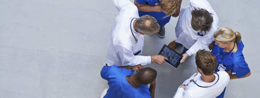 High angle view of a group of doctors standing around a digital tablet